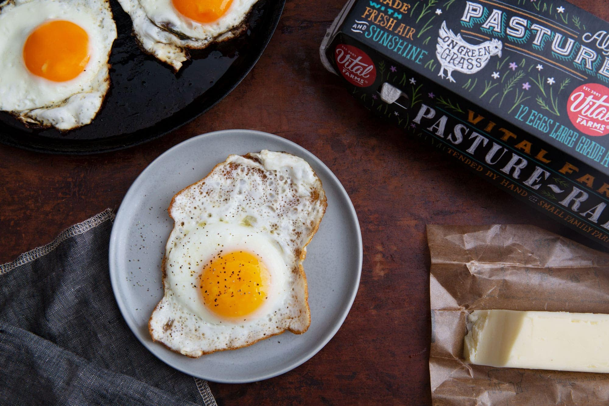 Two crispy fried eggs on a cast iron skillet in the upper left corner, a carton of pasture raised eggs and a stick of butter in the right corner and a crispy fried egg on a plate in the center of the table.