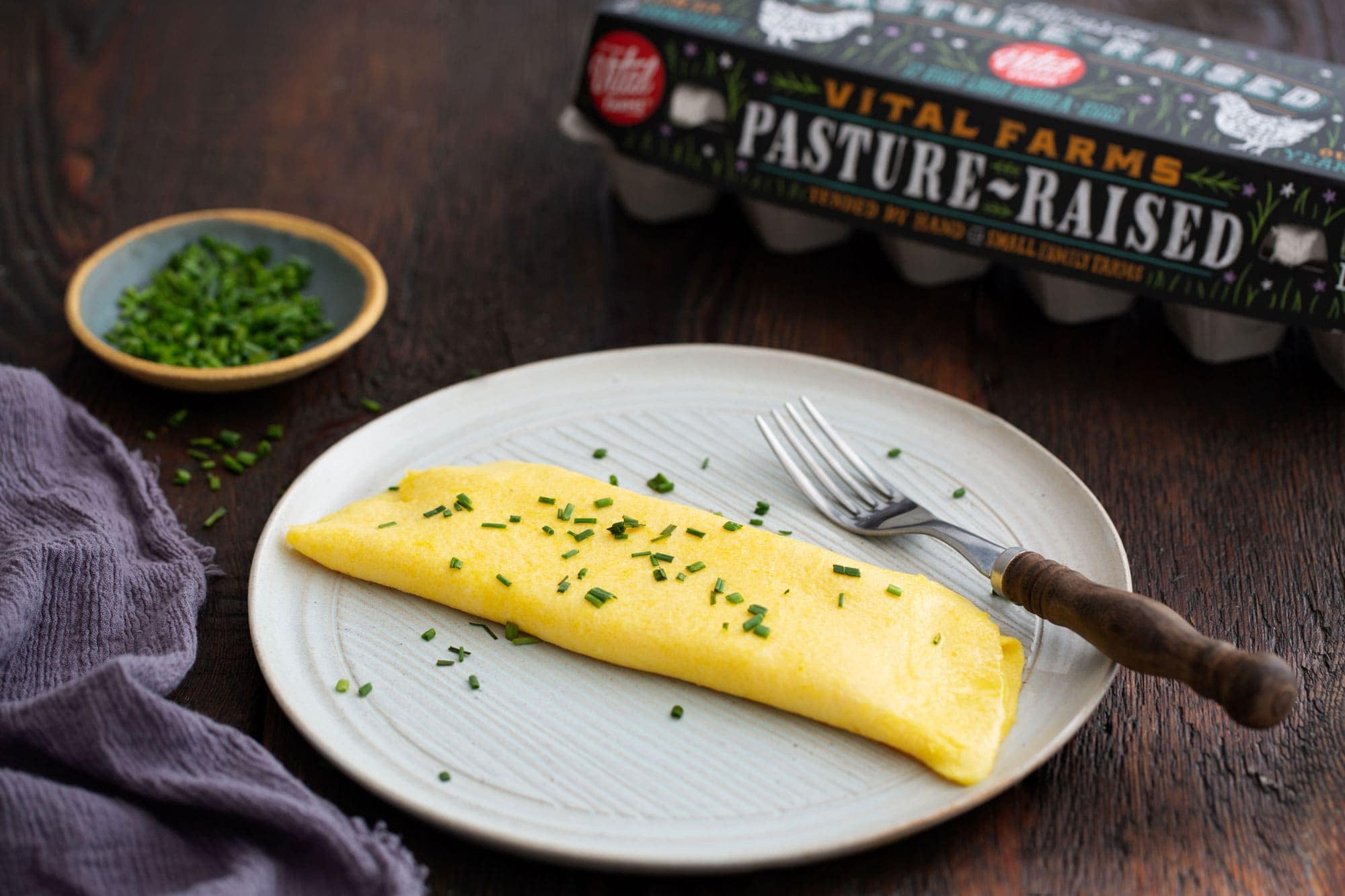 A beautiful looking omelet folded on a plate and sprinkled with chives. In the background there is a carton of pasture raised eggs.