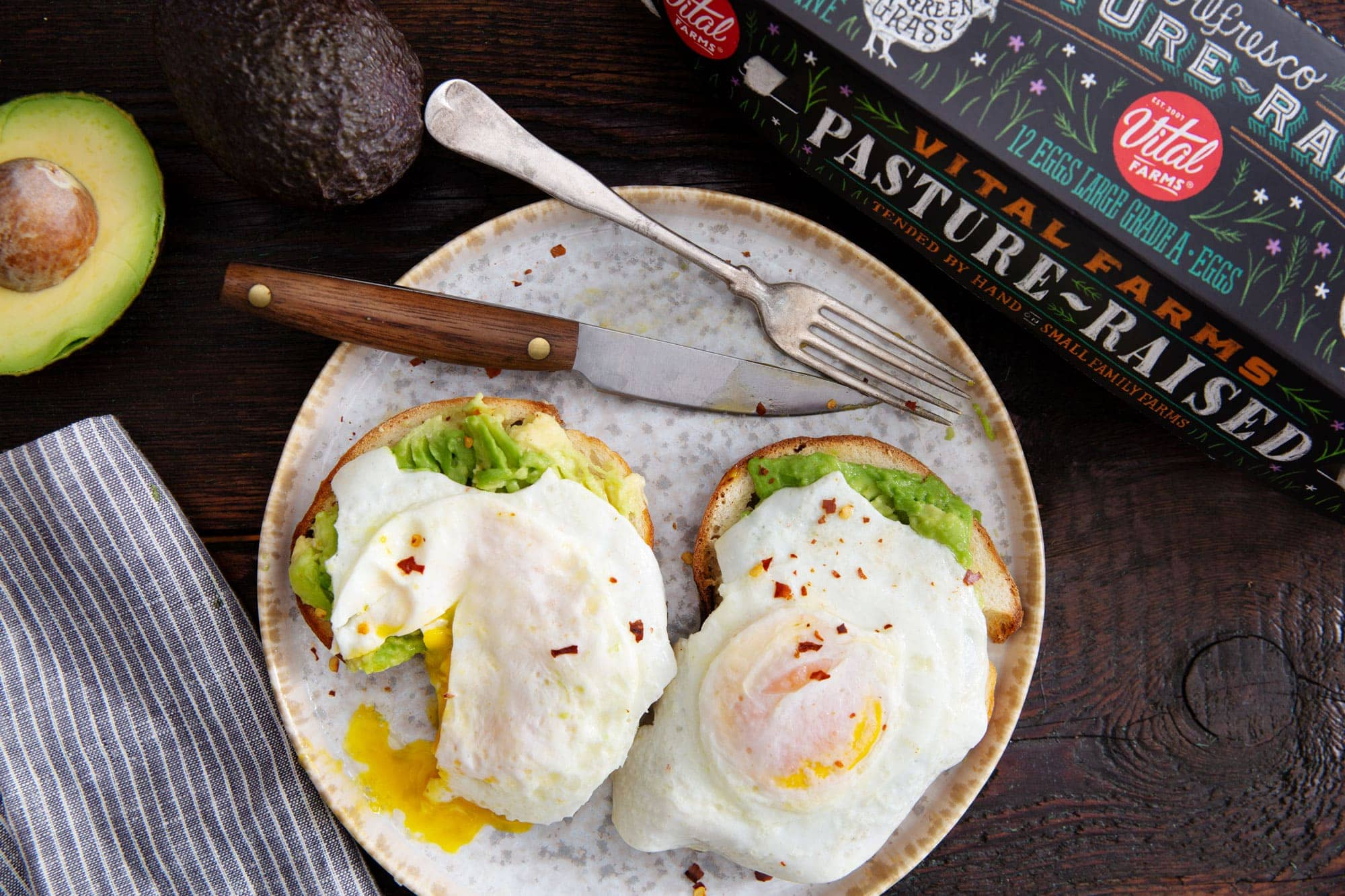 Over Easy eggs on top of avocado toast on a plate with Vital Farms egg carton and eggs and avocado nearby.