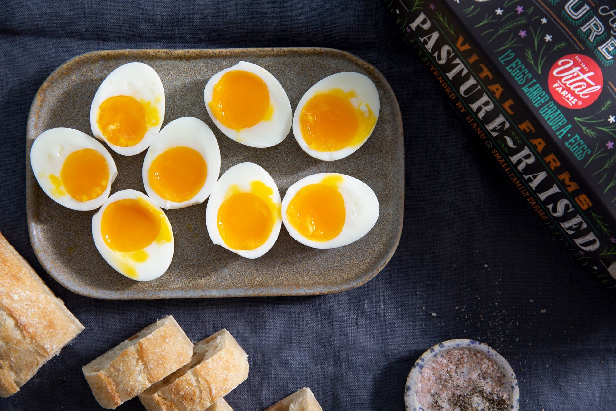 Four soft boiled eggs cut in half and displayed on on a table with a blue tablecloth with slices of baguette and salt cellar and a carton of Vital Farms Pasture raised eggs.