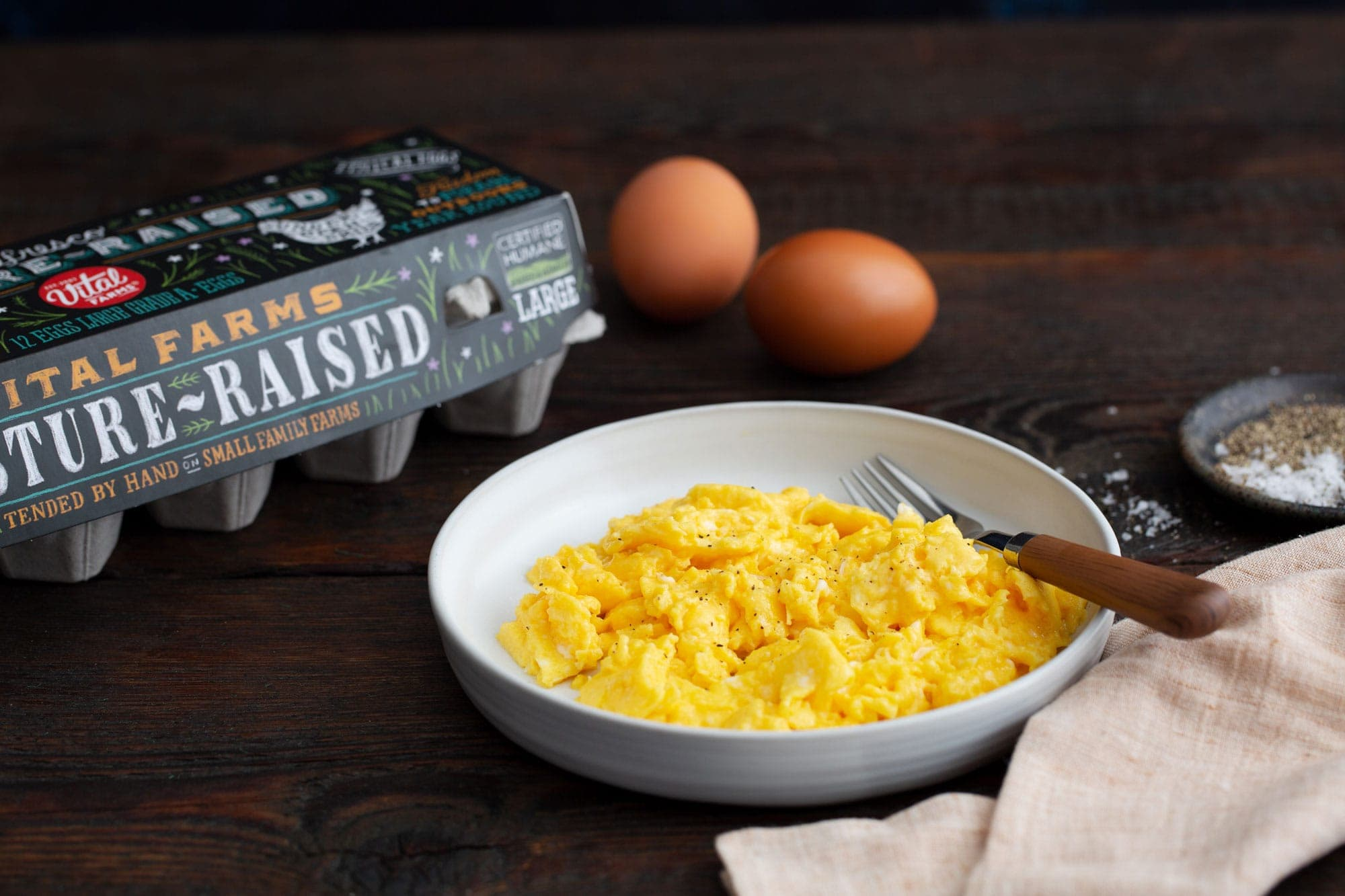 Scrambled Eggs in a dish on a wood counter with Vital Farms egg carton and eggs in the background.