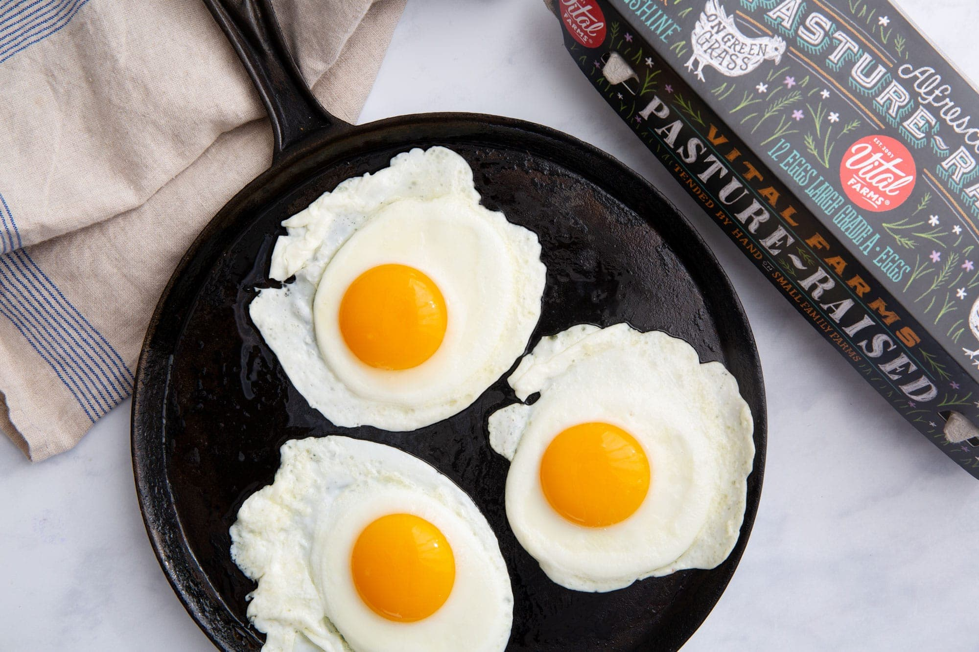 Three sunny side up eggs on a cast iron skillet next to a carton of pasture raised eggs.