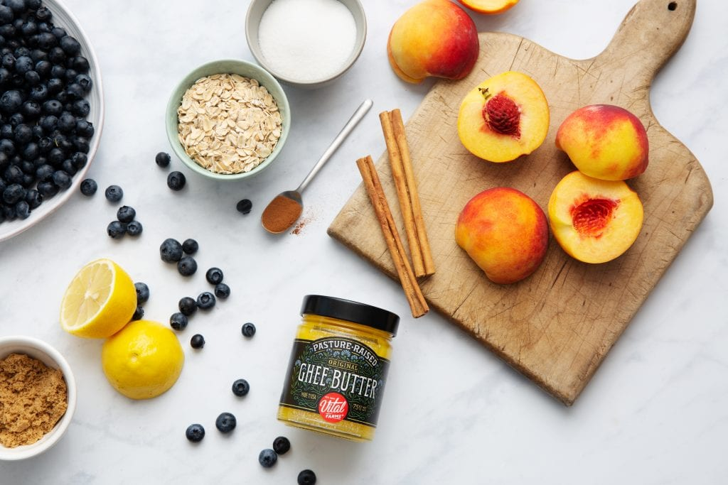 Vital Farms pasture raised ghee in a glass jar on a counter with sliced peaches and a bowl of oats and blueberries an cinnamon sticks
