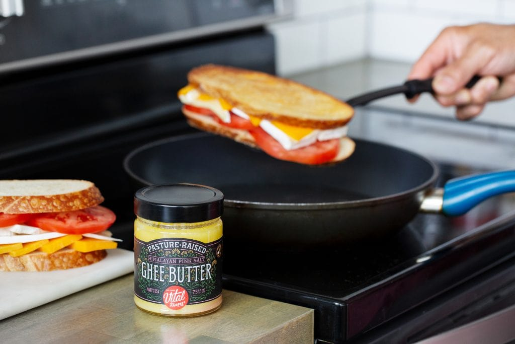 A person putting a grilled cheese on a skillet on the stove top with a glass jar of Vital Farms ghee next to it.