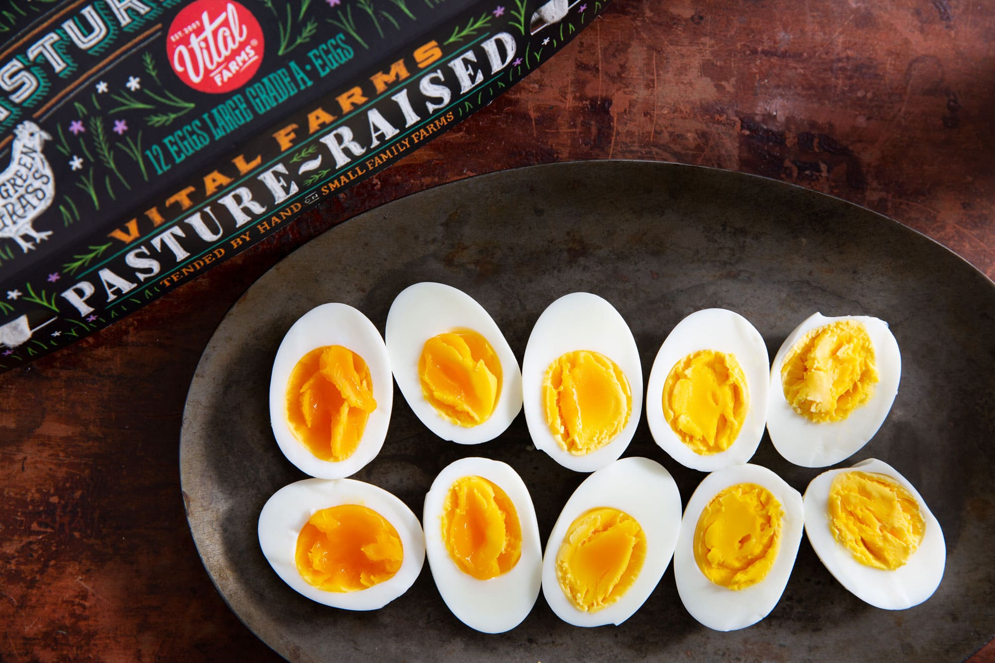 Five delicious looking hard boiled eggs cut in half and artfully displayed on a platter with a carton of Vital Farms pasture raised eggs.