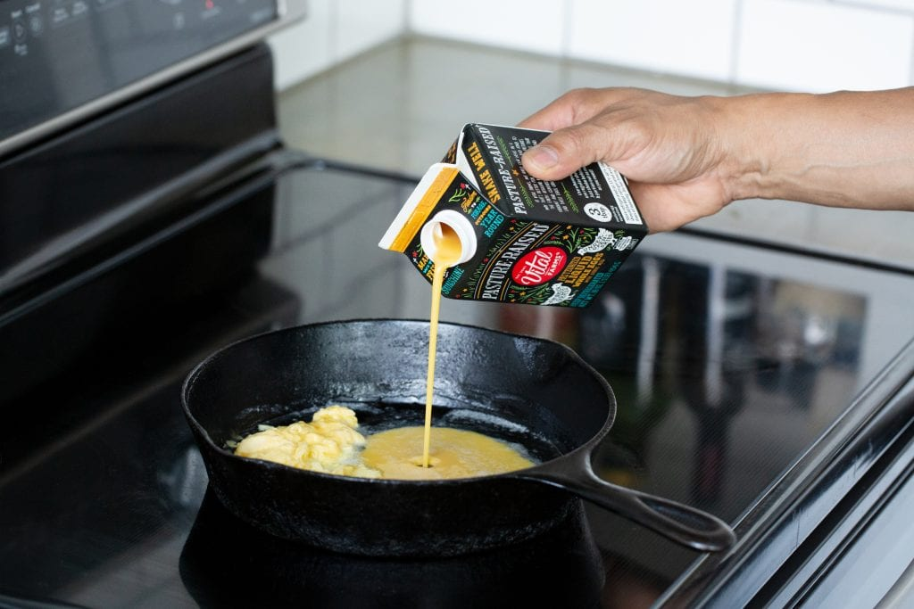 Image of a hand pouring a carton of Vital Farms Liquid eggs into a cast iron skillet on a stove top.