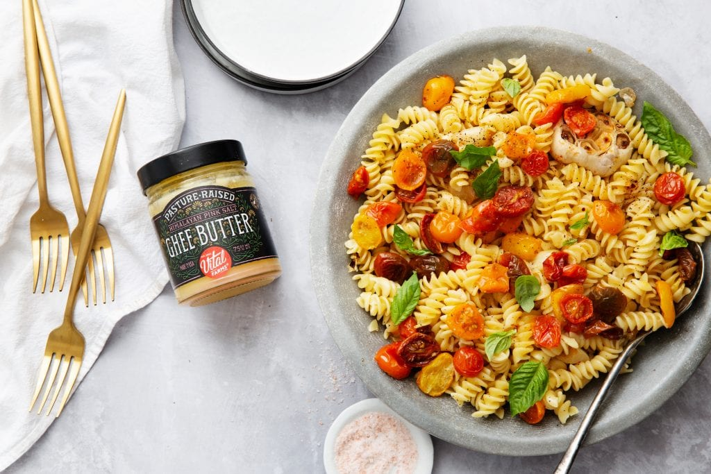 A bowl filled with spiral pasta and veggies and a jar of Vital Farms ghee next to it