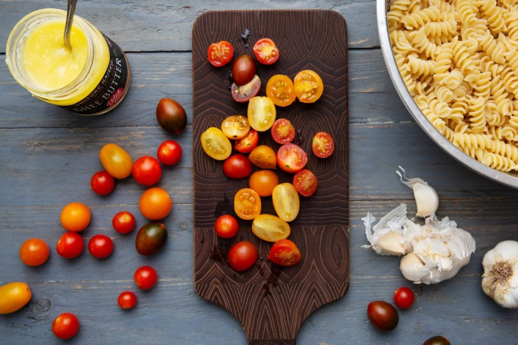 Sliced cherry tomatoes on a wooden cutting board with ghee in a glass jar and a bowl of spiral pasta next to them.
