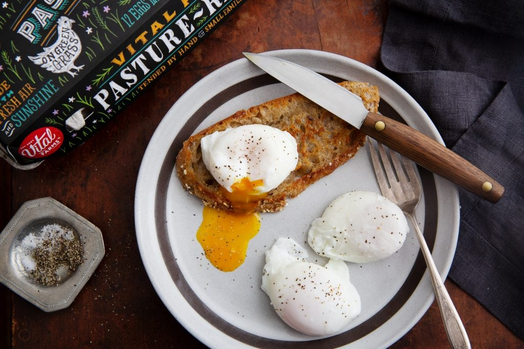 Poached eggs on a plate with a side of toast.