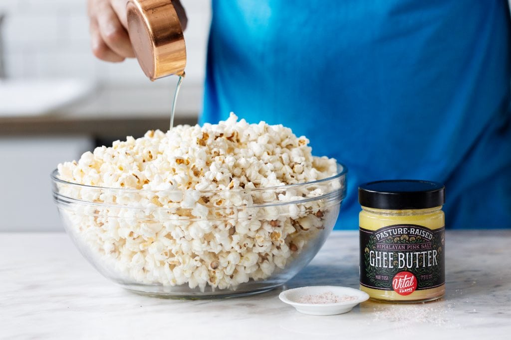 Vital Farms Ghee being poured over a bowl of popcorn in a glass bowl