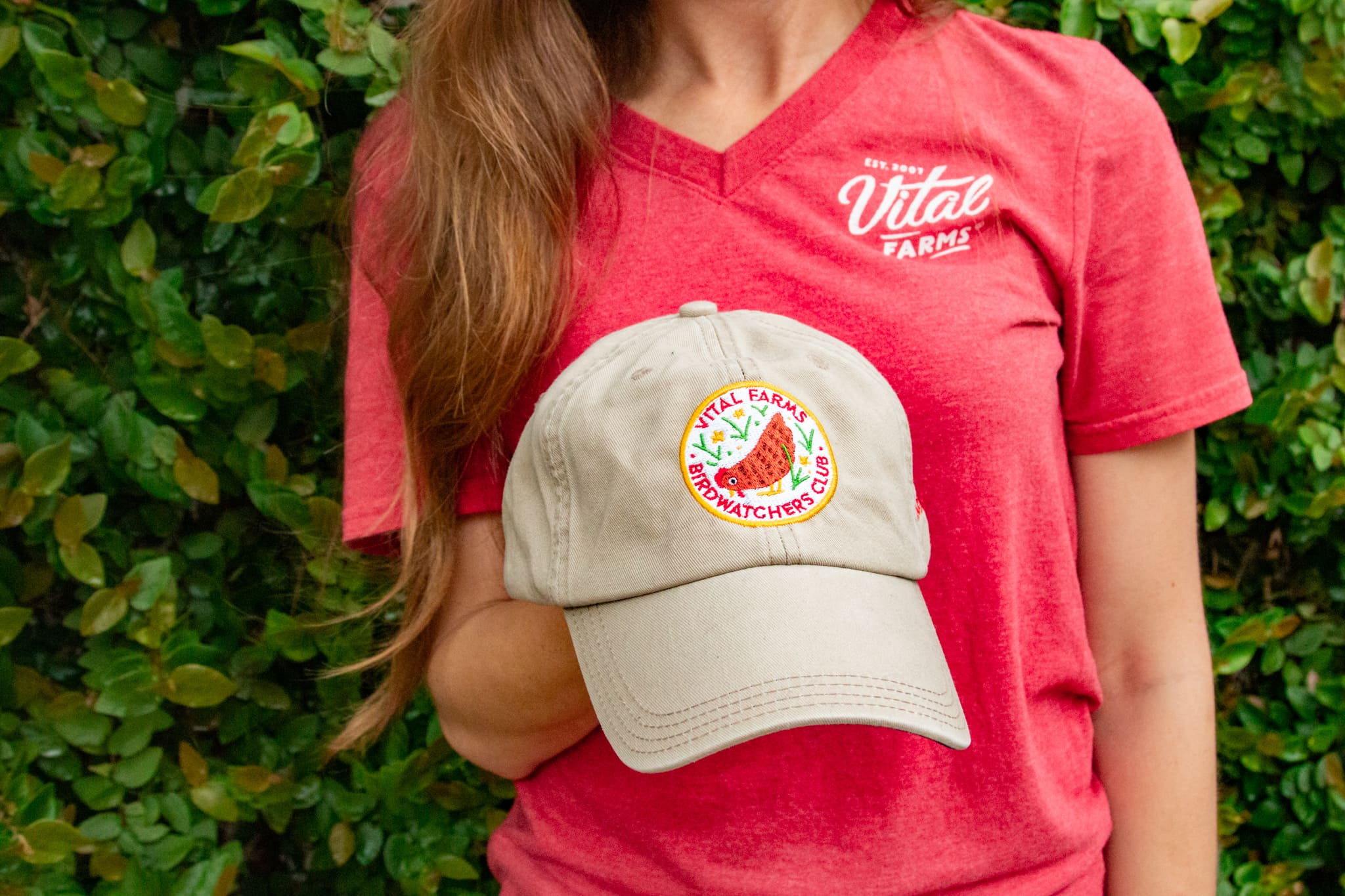A woman in a red t-shirt with a vital farms logo holding a vital farms birdwatchers baseball cap.