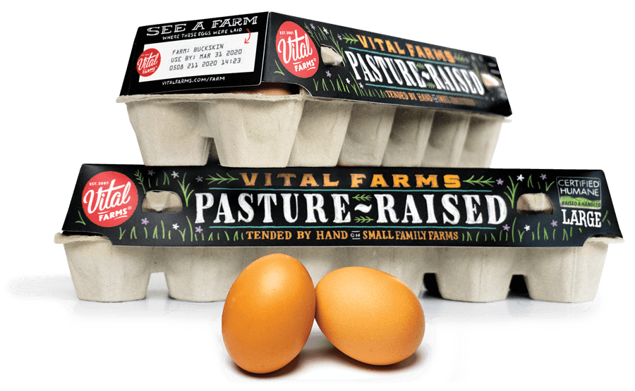 Stacked Cartons of Vital Farm Eggs and two brown eggs sitting in front.