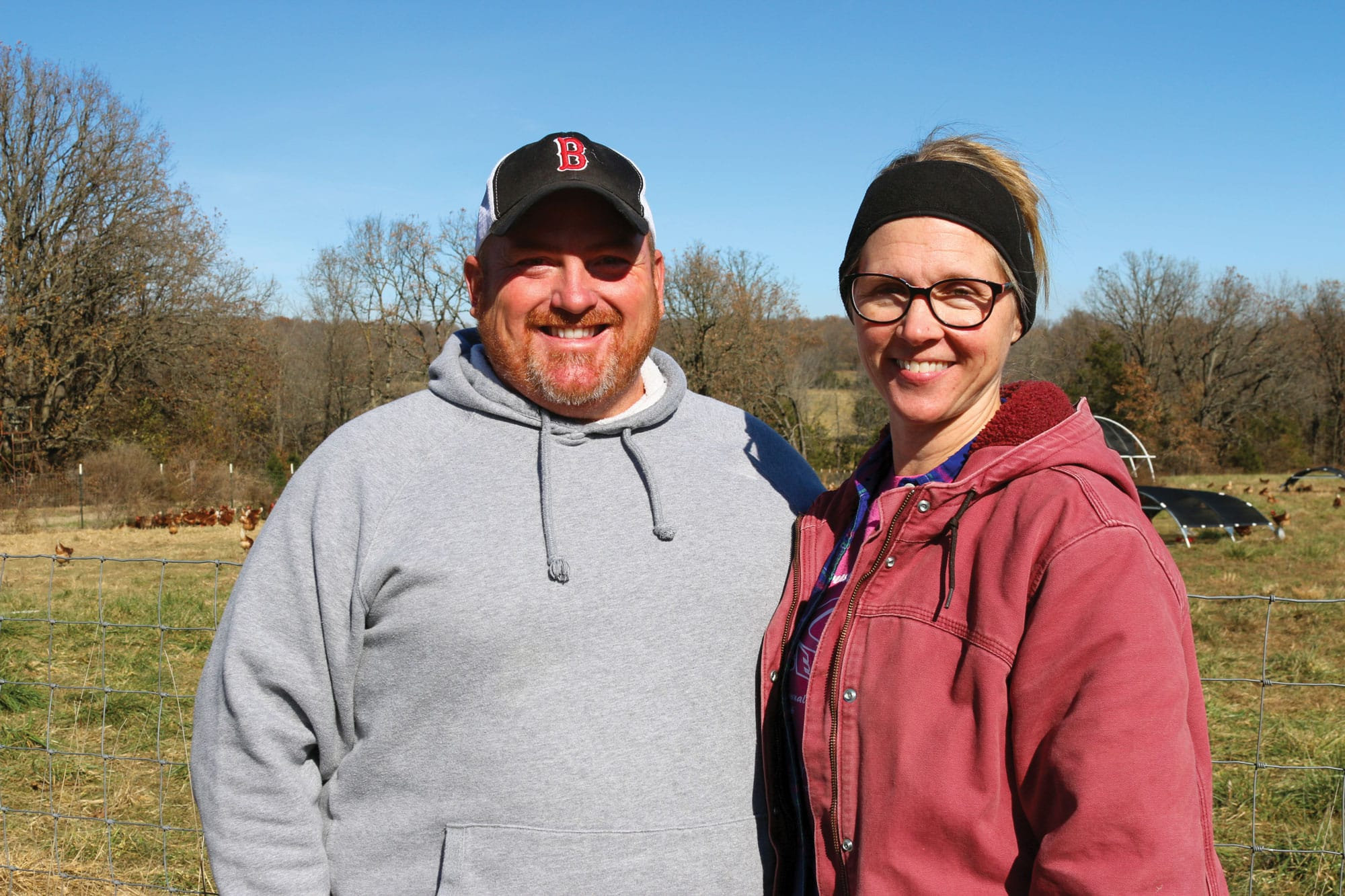 A portrait of Reggie and Missy, farmers from Buskin Acres, standing in a field near their chickens